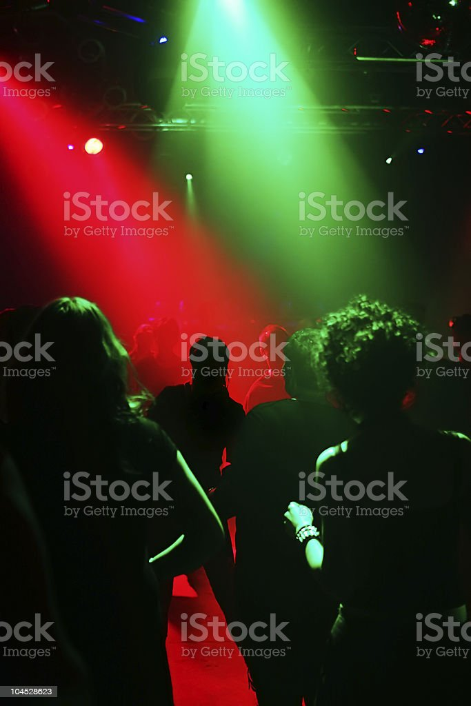 Silhouettes of teenagers in a disco royalty-free stock photo