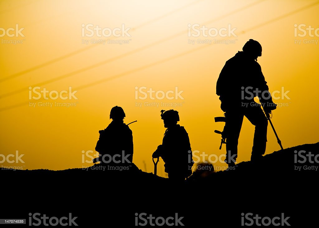Silhouettes of three soldiers on a hill stock photo