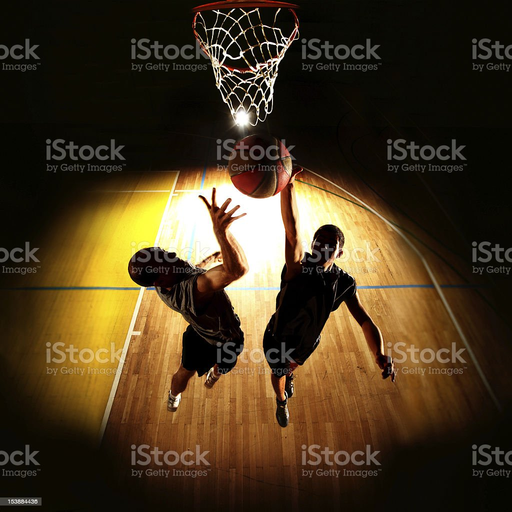 Silhouettes of two basketball players during a dunk stock photo