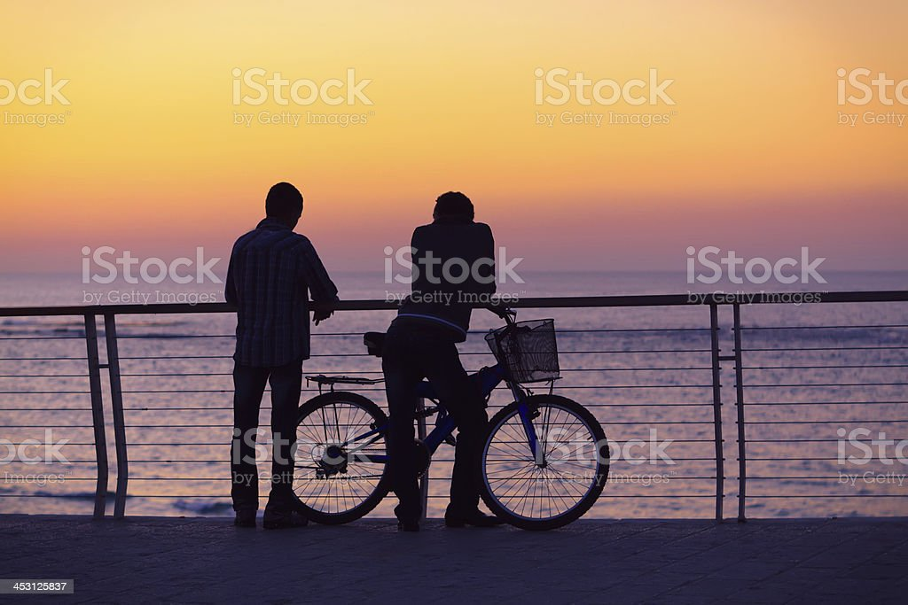 Silhouettes of two men with a bicycle stock photo