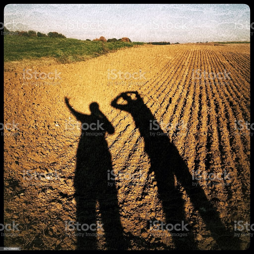 Silhouettes of two people against a plowed field stock photo