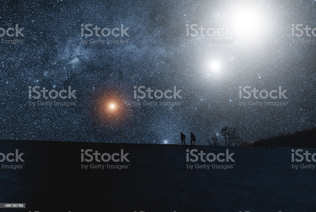 Silhouettes of two people walking amongst the stars stock photo