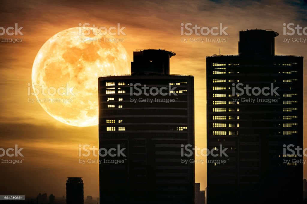 Silhouettes of two skyscrapers construction with supermoon. stock photo
