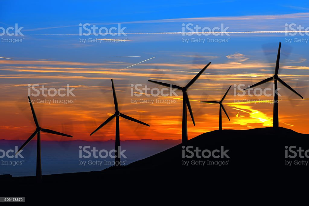 Silhouettes of Wind Turbines at Sunset stock photo