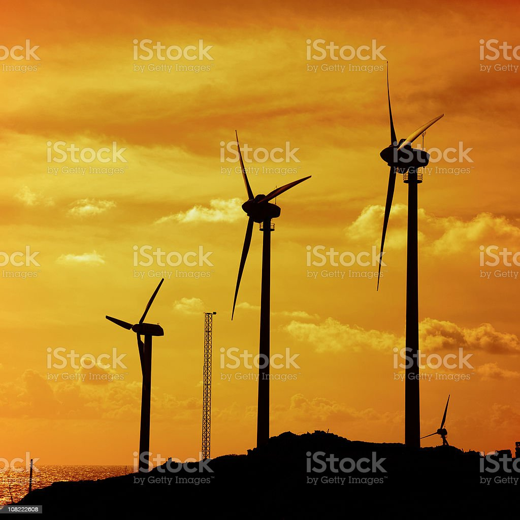 Silhouettes of Wind Turbines on Hill at Sunset royalty-free stock photo