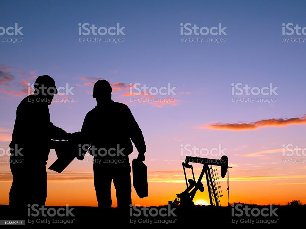 Silhouettes of workers and oil pump during sunset stock photo