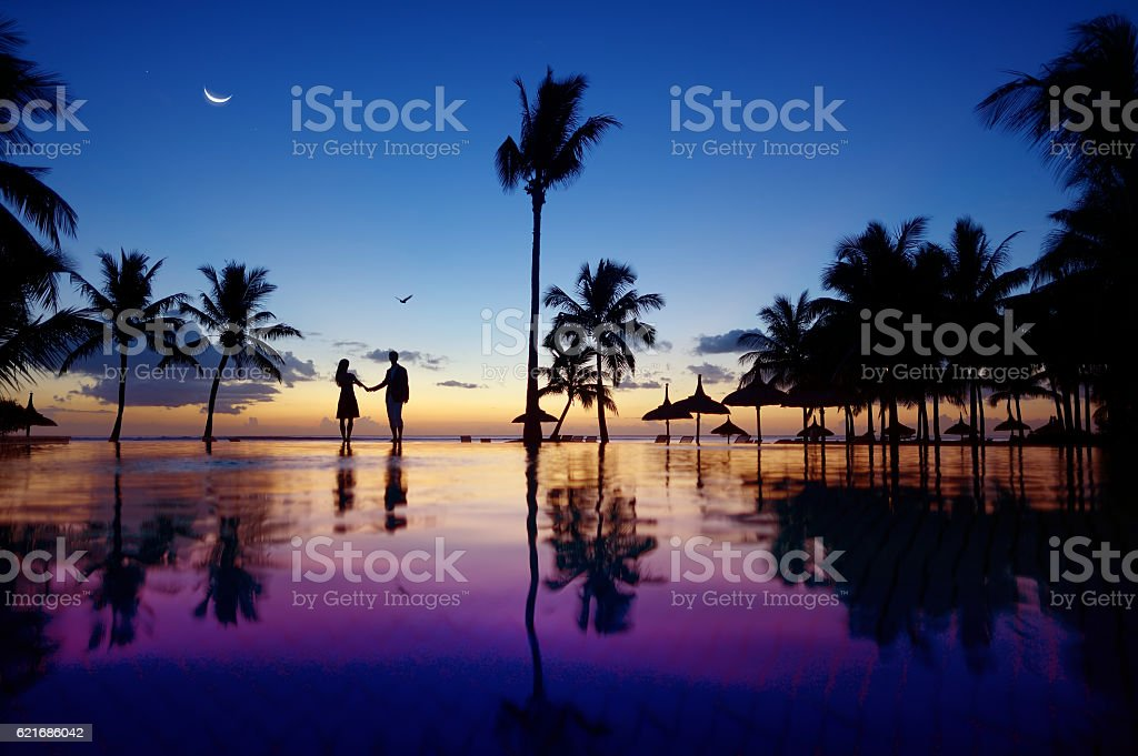 Silhouettes of young couple at scenic sunset stock photo