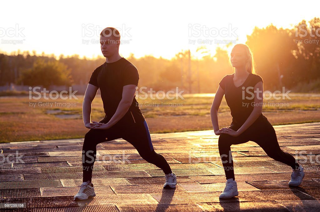 Silhouettes of young sporty man and woman outdoors stock photo