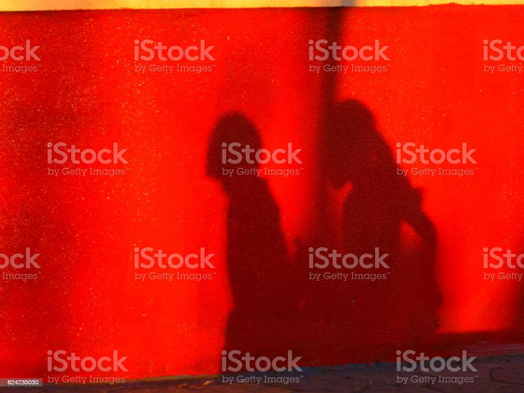 Silhouettes on a red wall stock photo