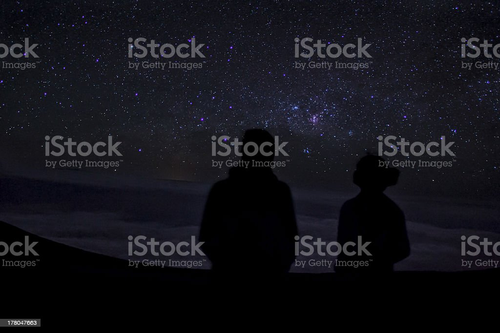 Silhouettes on two people star gazing stock photo
