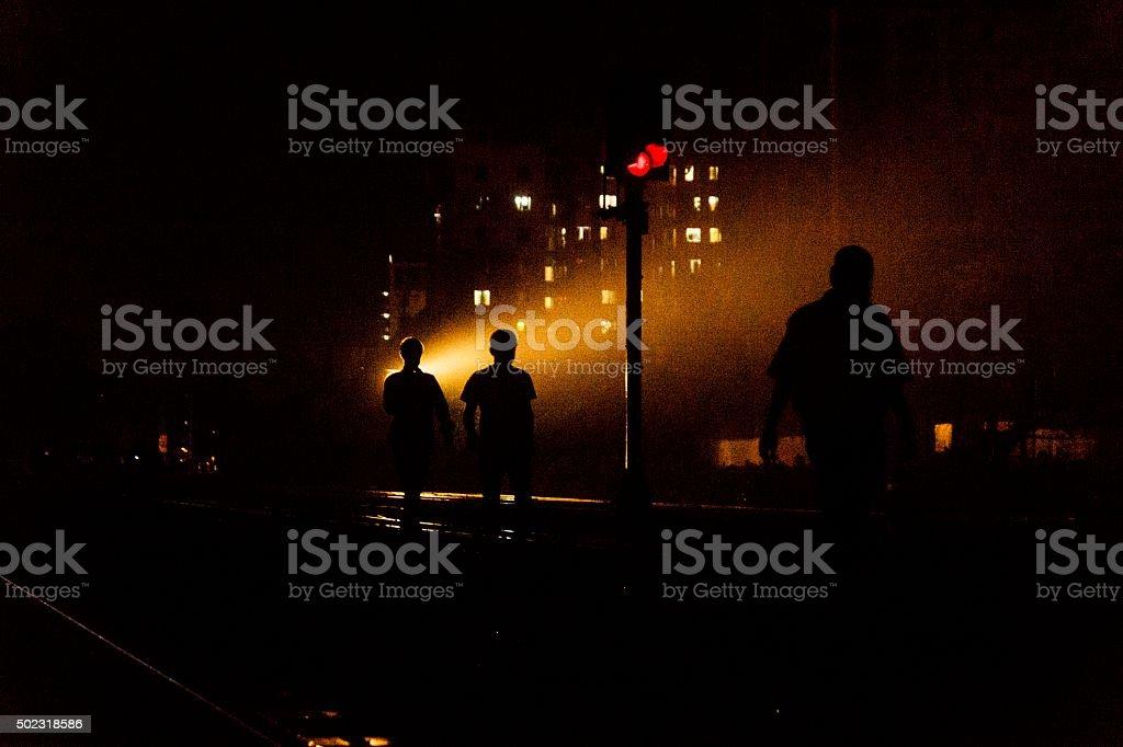Silhouettes walking along train track. stock photo