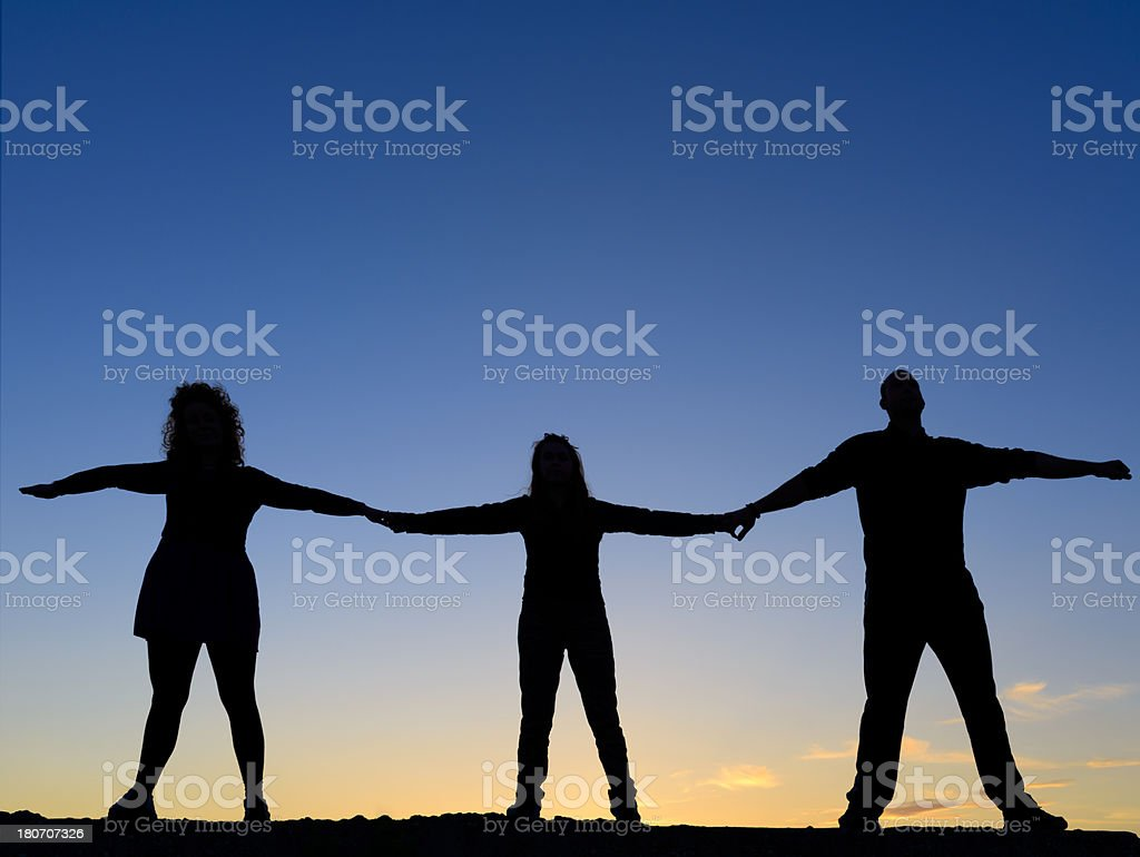 silhouettes with arms raised royalty-free stock photo