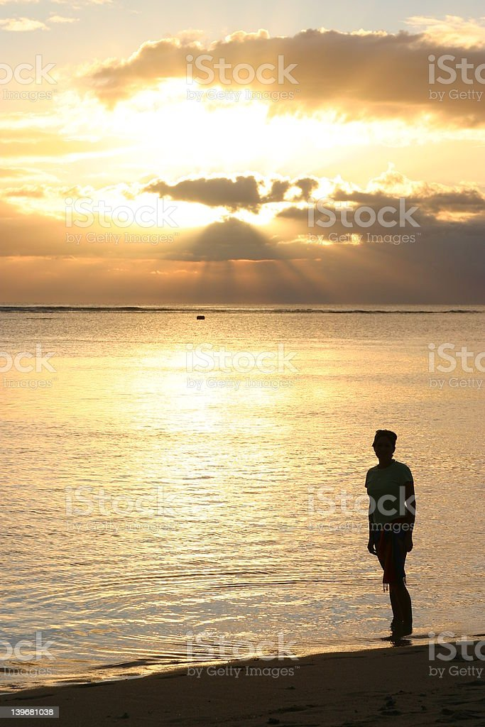 Silhoutte of woman standing on a beach royalty-free stock photo