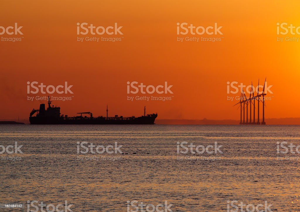 Silhuette of ship and wind turbines in orange sunset. royalty-free stock photo