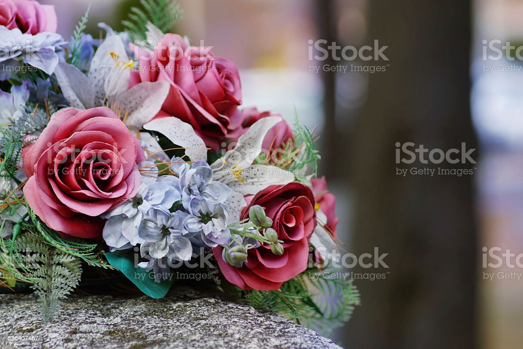 Silk flowers on a gravestone, soft focus stock photo