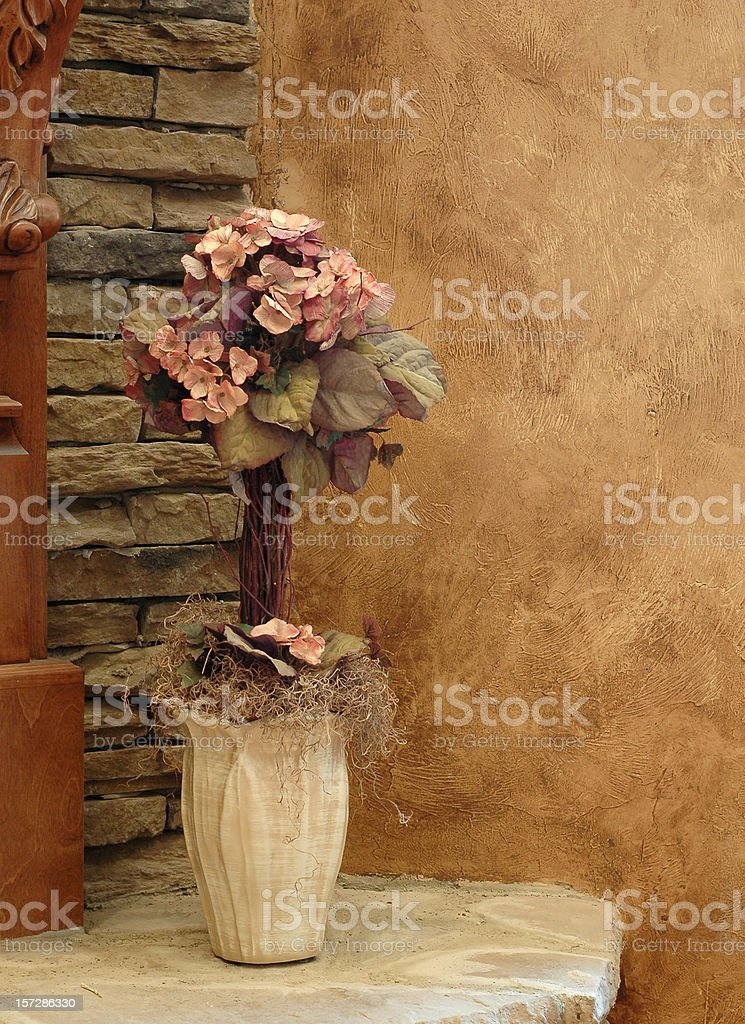 Silk Flowers, Rock Hearth & Faux Brown Wall stock photo