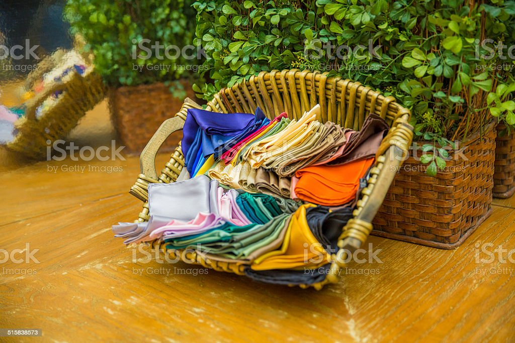 Silk Pocket Squares, handkerchiefs, in a basket on a wooden table