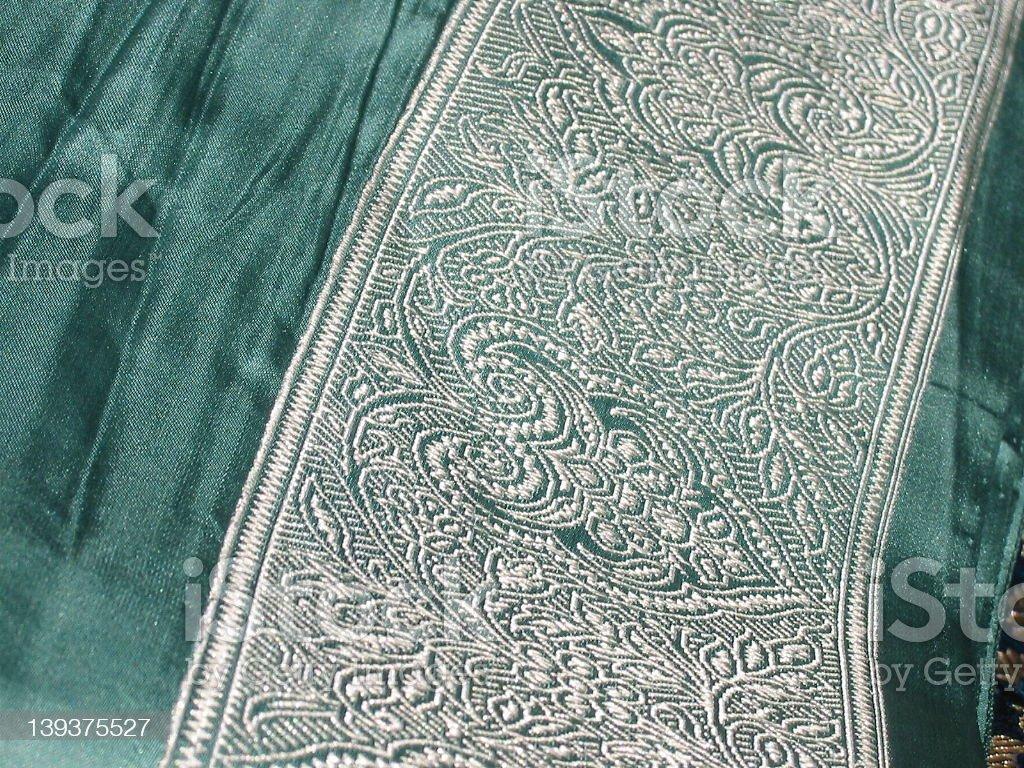 silk sari border, white embroidered pattern on green royalty-free stock photo