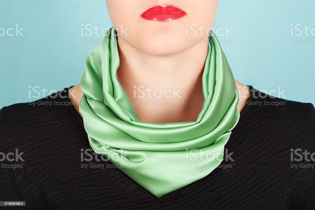 Silk scarf. Green silk scarf around her neck isolated on blue background. stock photo