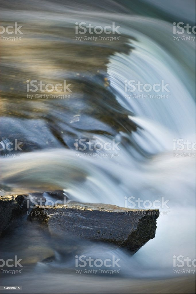 Silky, motion-blurred rushing river over sharp rocks (abstract) royalty-free stock photo