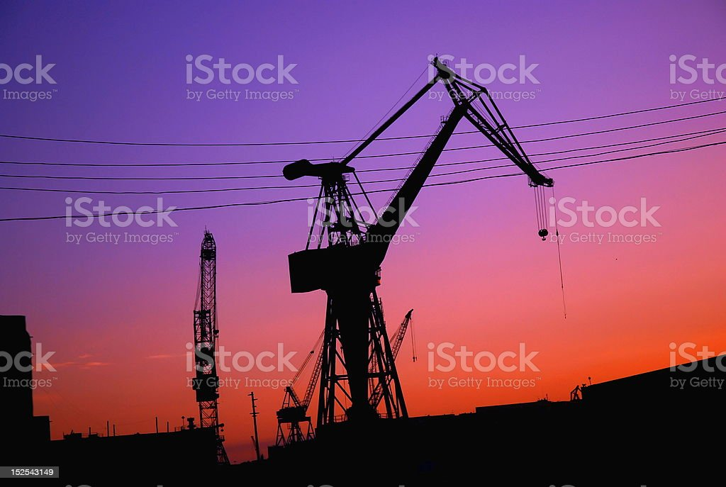 Sillhuettes Of Industrial Cranes At Sunrise royalty-free stock photo