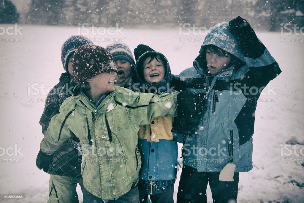 Silly children playing in a snowstorm in jackets and hats stock photo