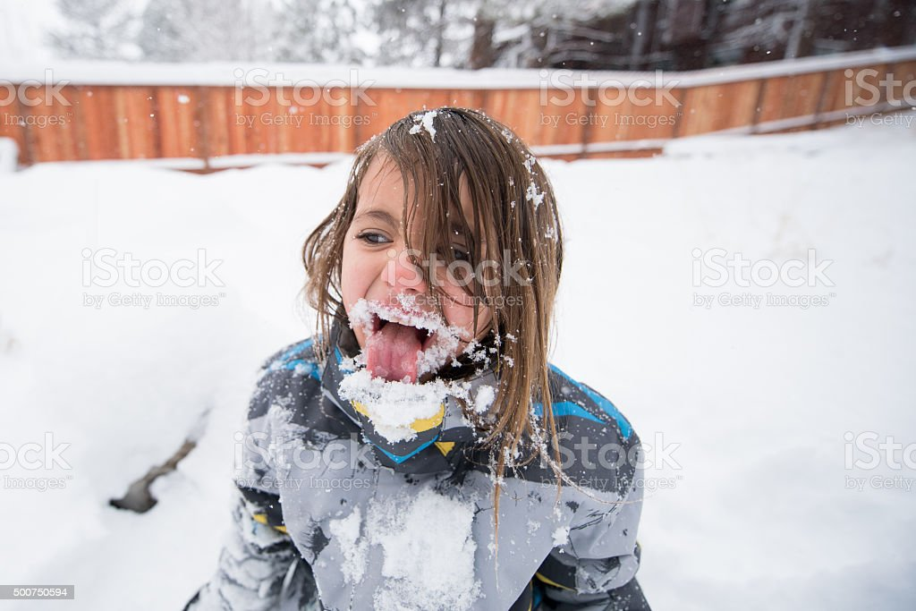 Silly girl eating snow stock photo