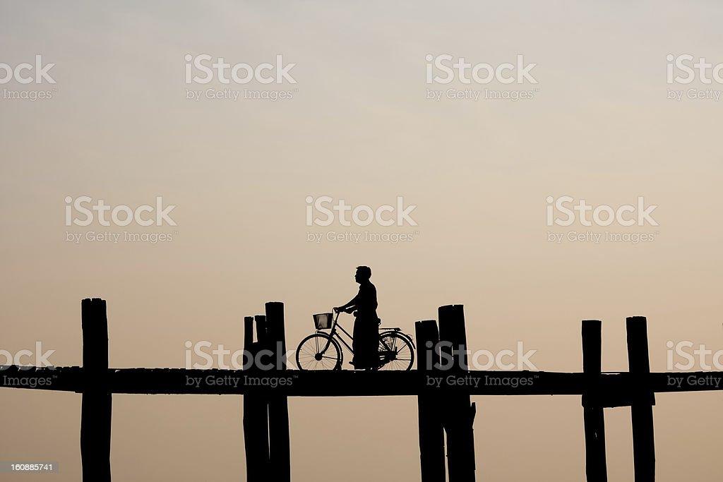 Silouhette of Burmese crossing U Bein Bridge, Burma stock photo