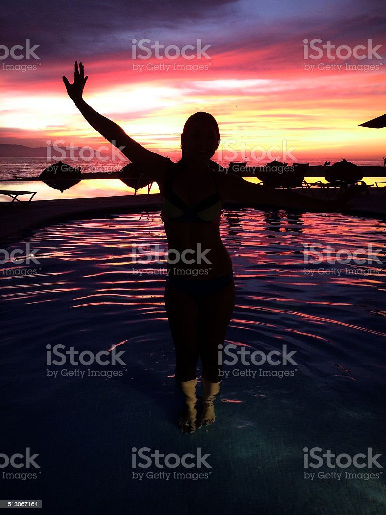 Siloutte of gorgeous woman at sunset in an infinity pool stock photo