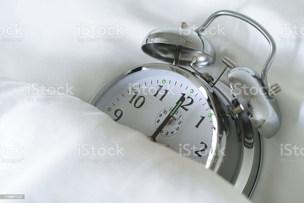 Silver alarm clock tucked up in bed stock photo