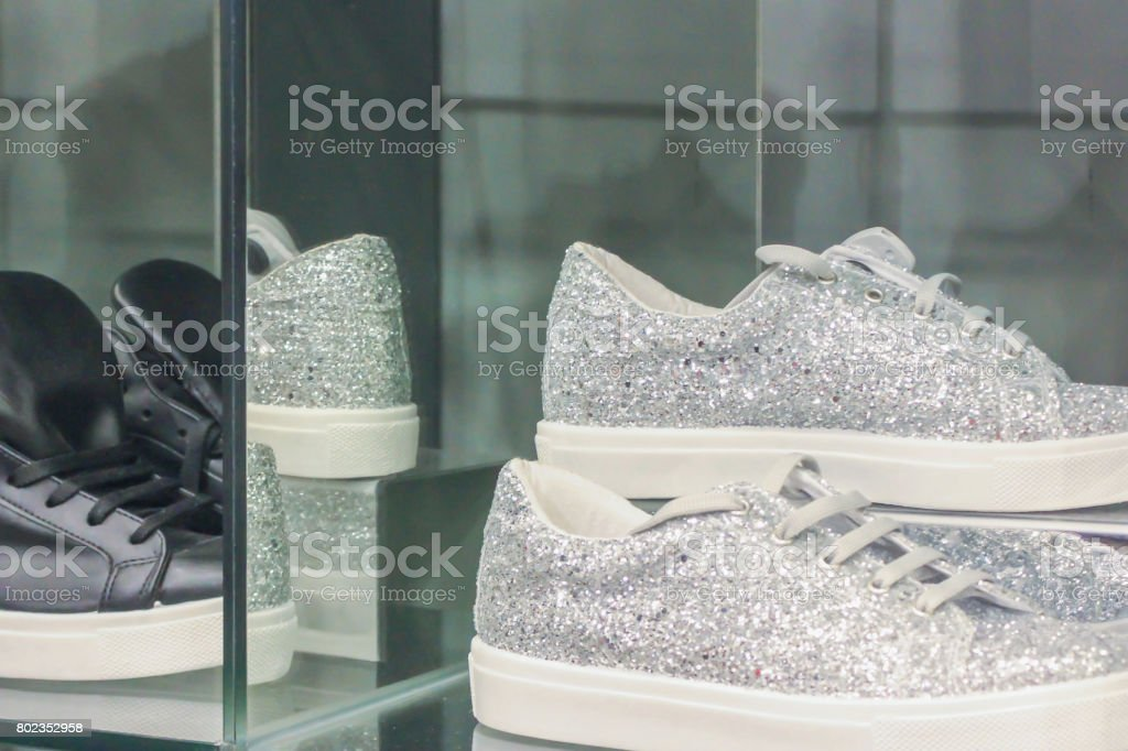 Silver and black sneakers in womens store stock photo