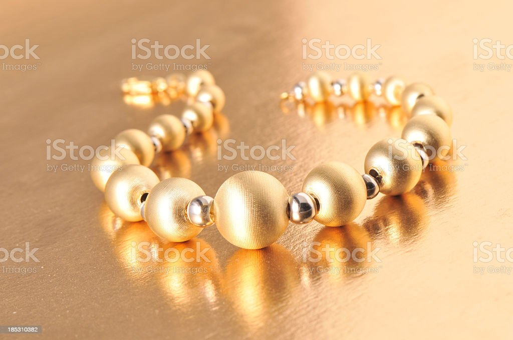 Silver and gold colored bracelet on a table stock photo