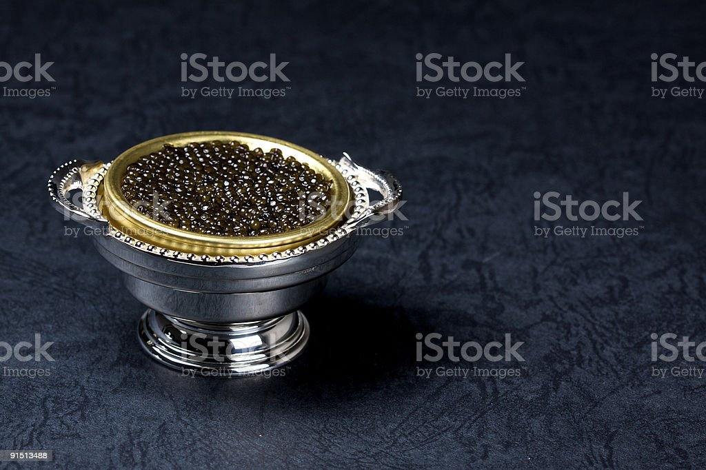 Silver and gold dish of caviar on dark blue background stock photo