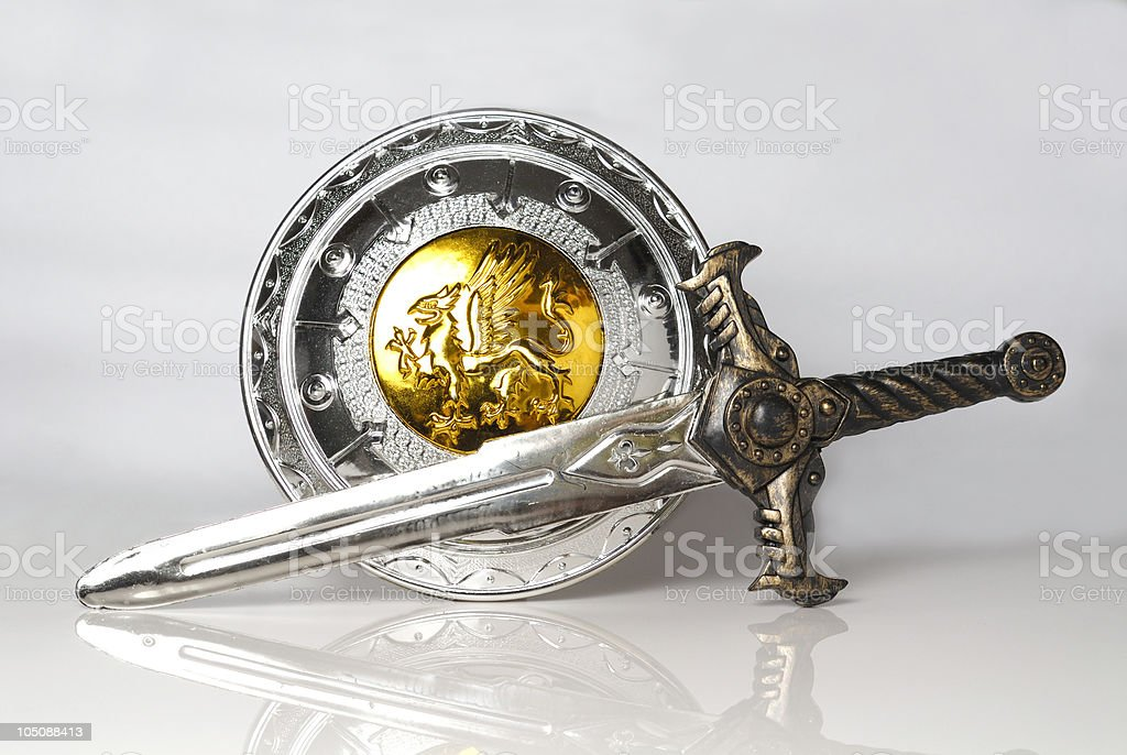 Silver and gold shield and sword against white background stock photo