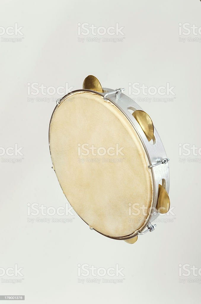 Silver and gold tambourine on light grey background stock photo