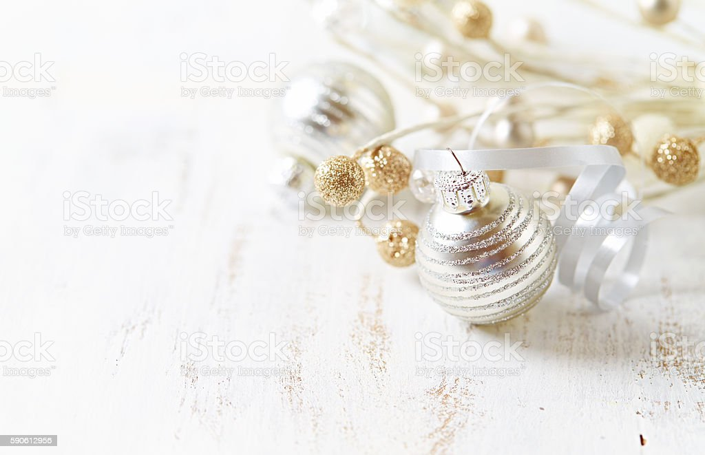 Silver and golden Christmas ornaments on a white wooden background stock photo