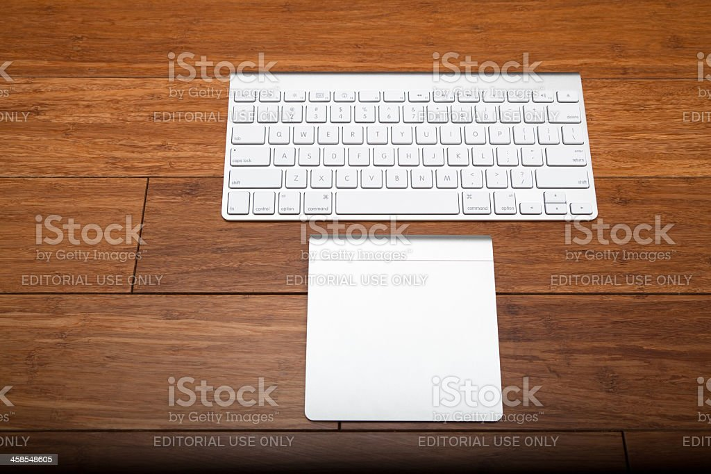 Silver Apple keyboard on wooden floor royalty-free stock photo