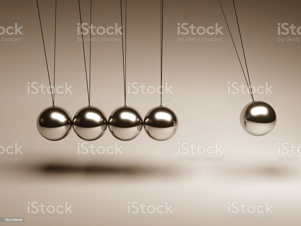 Silver balls on strings in a Newton's cradle stock photo