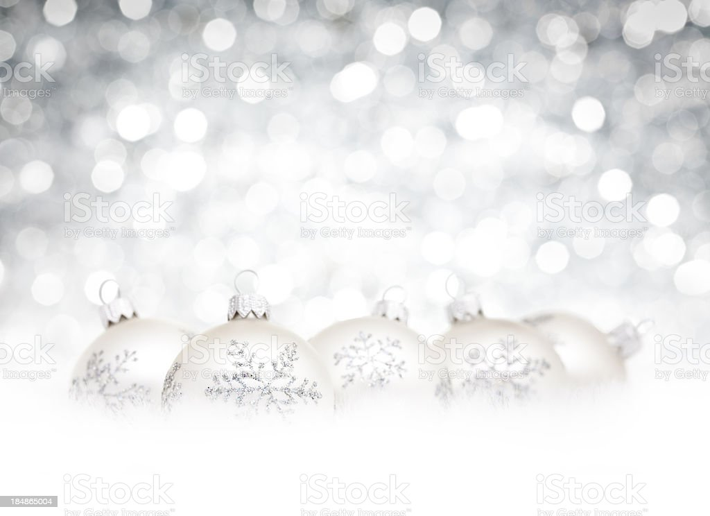 Silver Baubles on snow and white defocused christmas lights royalty-free stock photo