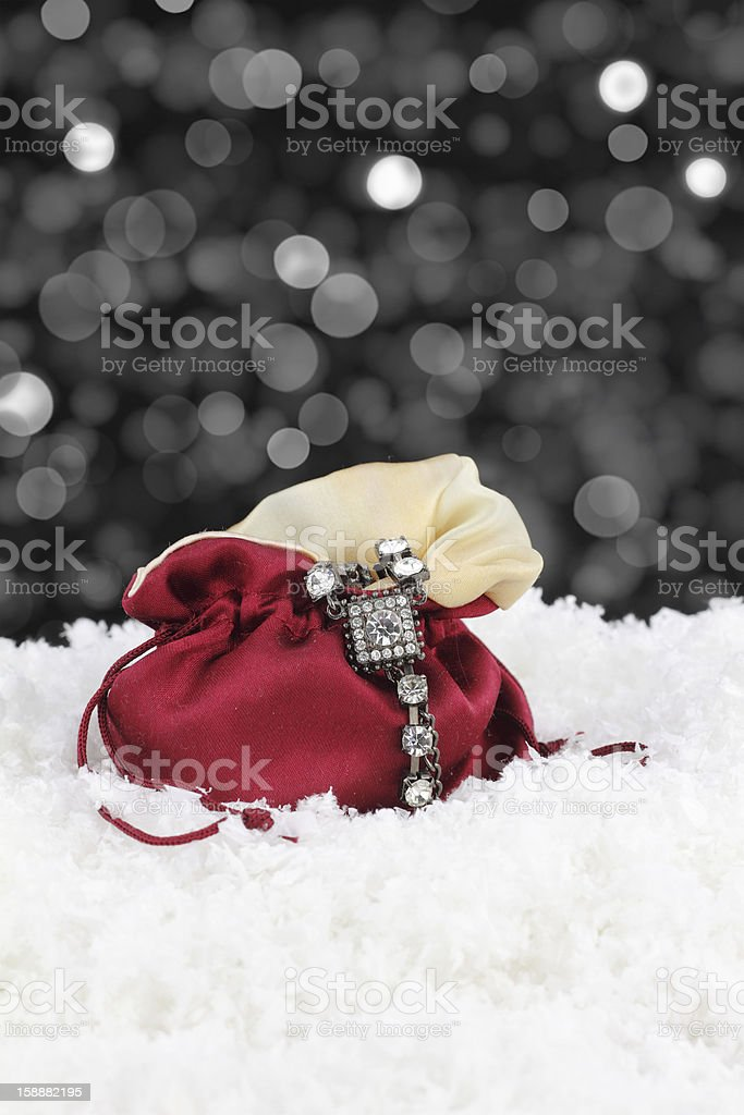 Silver bracelet draped on red satin pouch in snow royalty-free stock photo
