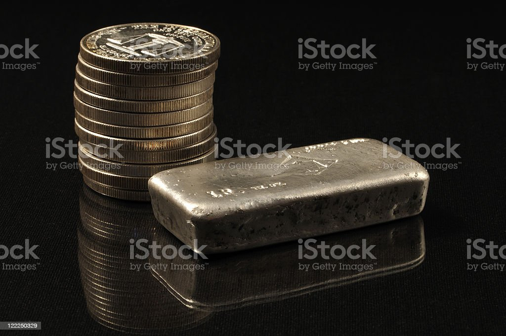 Silver bullion next to stack of silver coins royalty-free stock photo