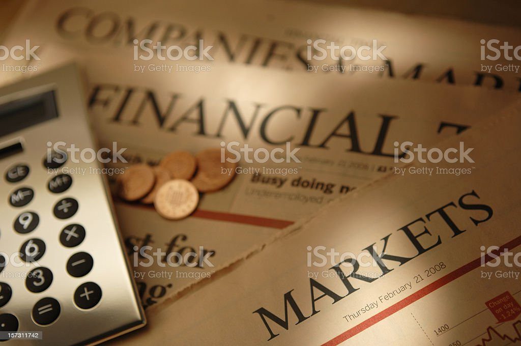 Silver Calculator And Coins On Financial Newspapers stock photo