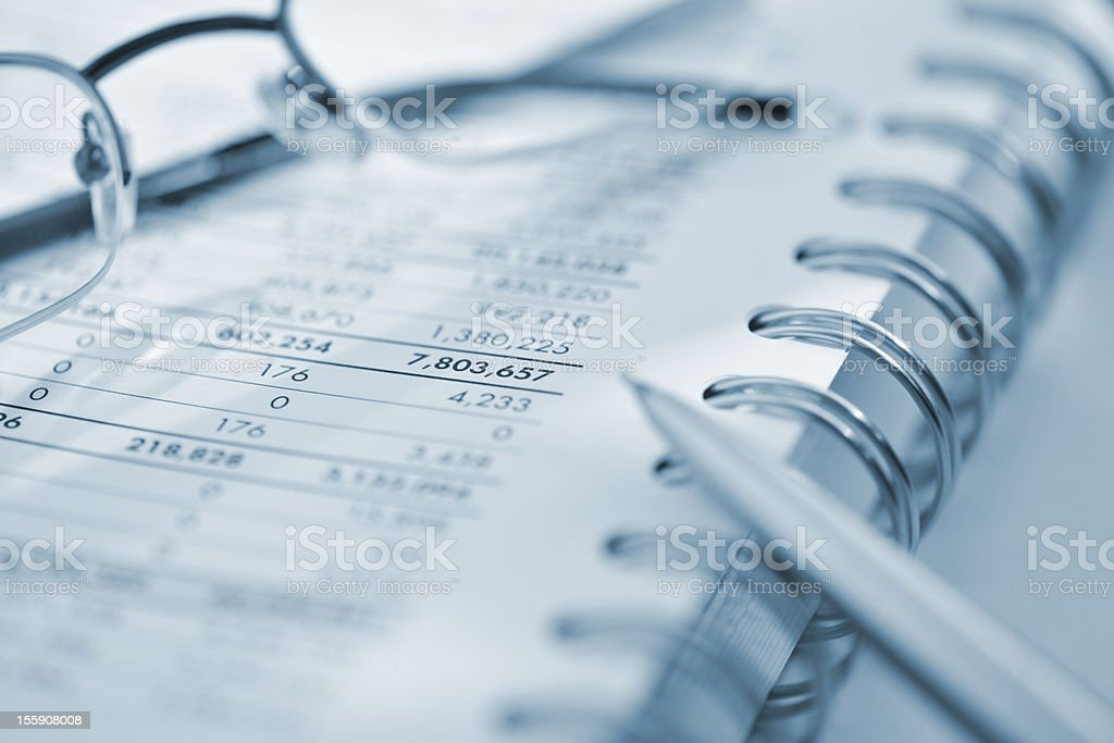 silver calculator and glasses on sheet of financial data royalty-free stock photo