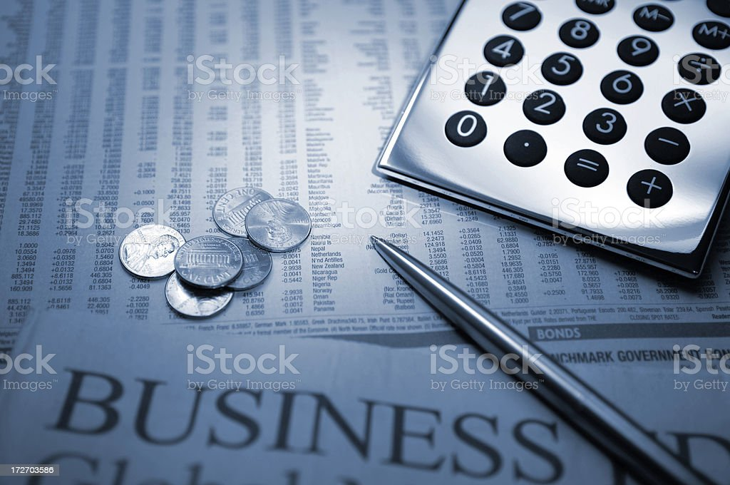 Silver Calculator, Coins and Pen on Financial Newspapers royalty-free stock photo
