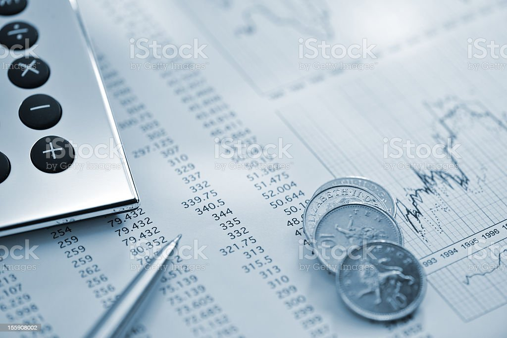 silver calculator, pen and coins on sheet of financial data royalty-free stock photo