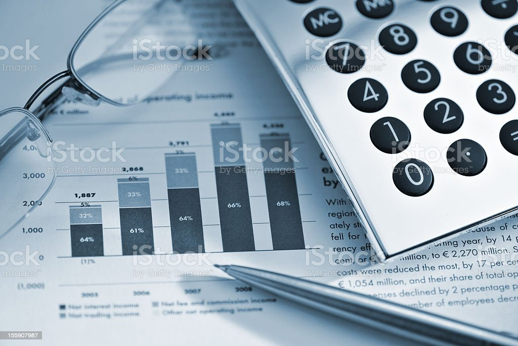 silver calculator, pen and glasses on sheet of financial data royalty-free stock photo