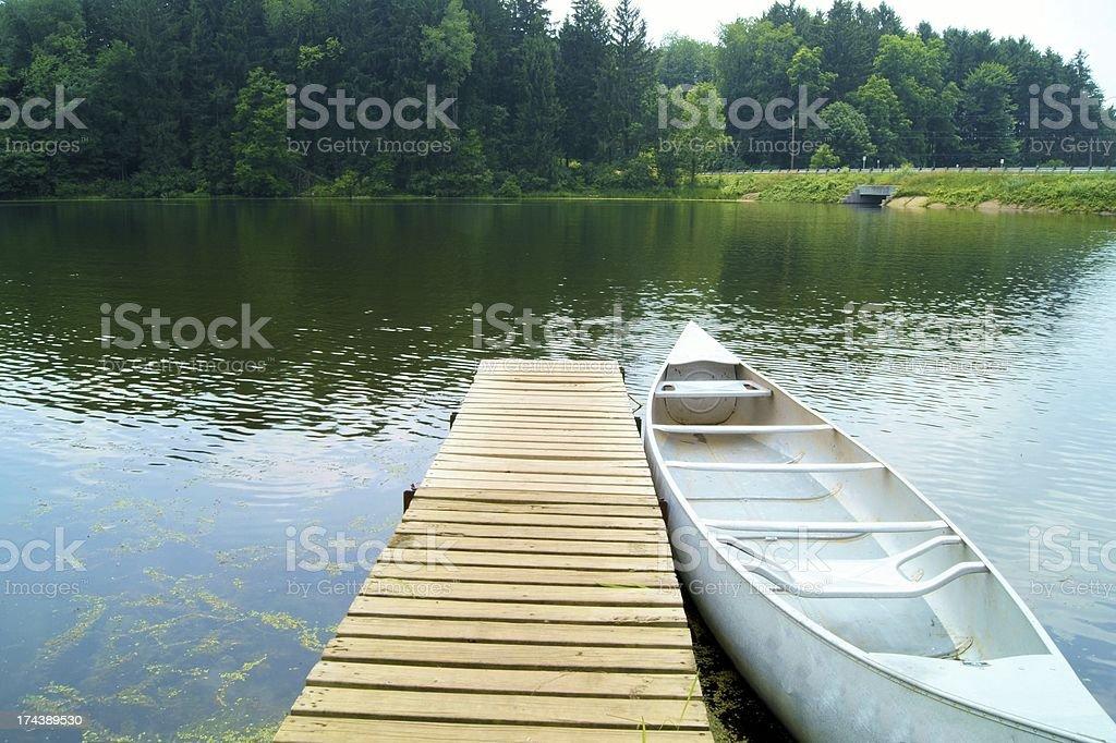 Silver canoe at dock on lake. stock photo
