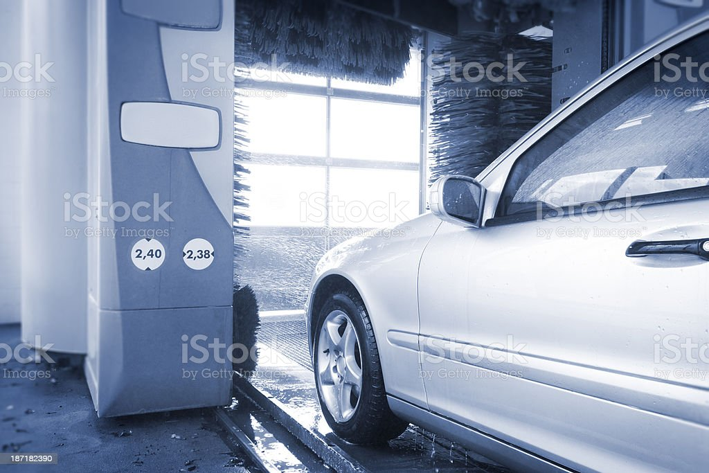silver car entering automatic car wash with brushes stock photo