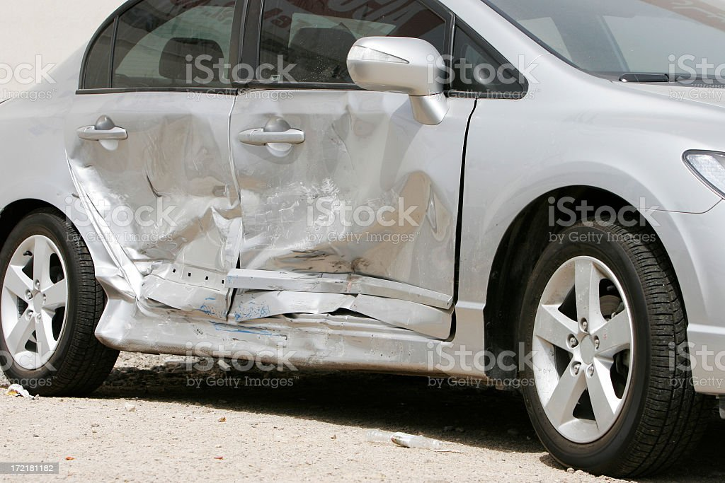 Silver car with a large dent in the side, ruining two doors royalty-free stock photo