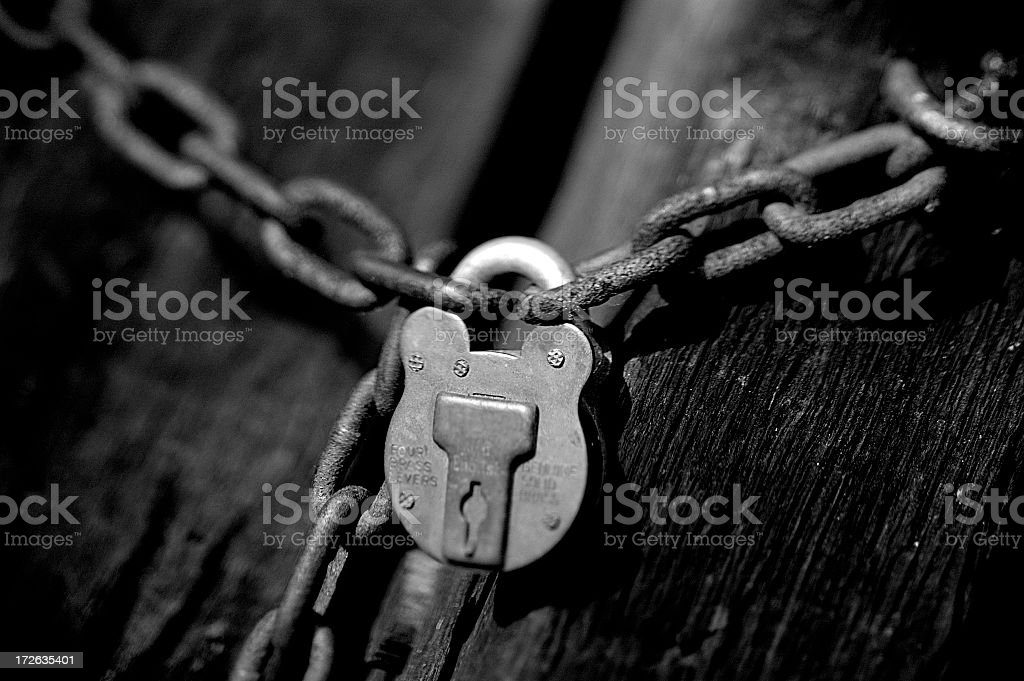 A silver chain connected by a silver padlock on a black door stock photo